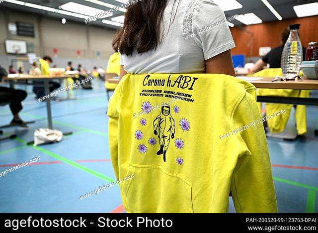 """20 May 2020, Baden-Wuerttemberg, Ravensburg: A yellow hoodie that says """"""""Corona hAbi - stayed home, got it anyway."""""""" hangs over the chair of a student who is..."""