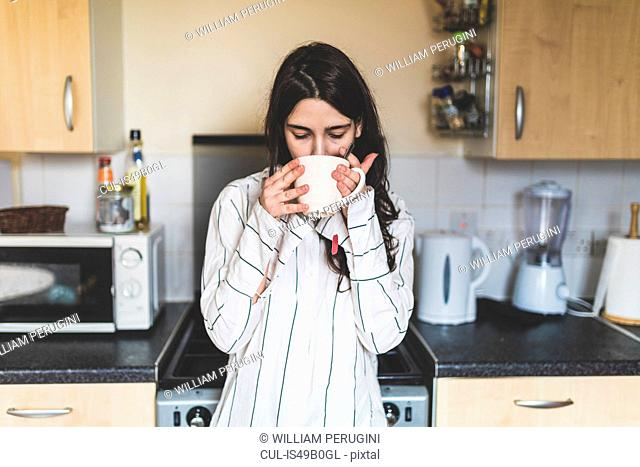 Young woman at home, in kitchen, wearing pyjamas, drinking cup of coffee