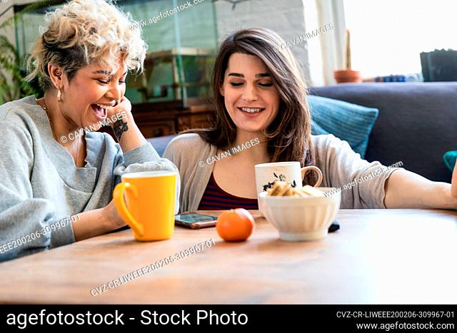 Happy female roommates using smart phone while having coffee at table