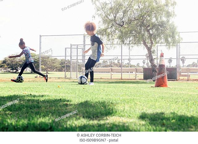 Schoolgirls doing dribbling soccer ball practice on school sports field