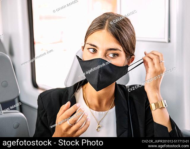 Businesswoman putting on mask in train