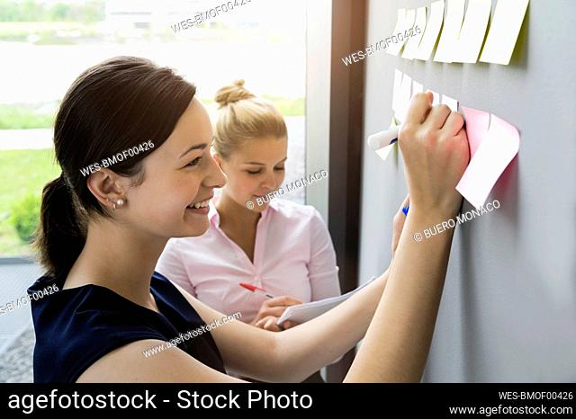 Smiling businesswoman writing on adhesive note stuck on wall while discussing with coworker in office