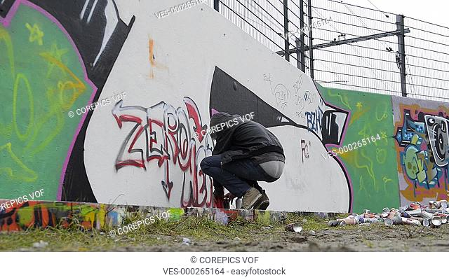 Graffiti artist being disturbed during spray painting, looking up from his work and running away