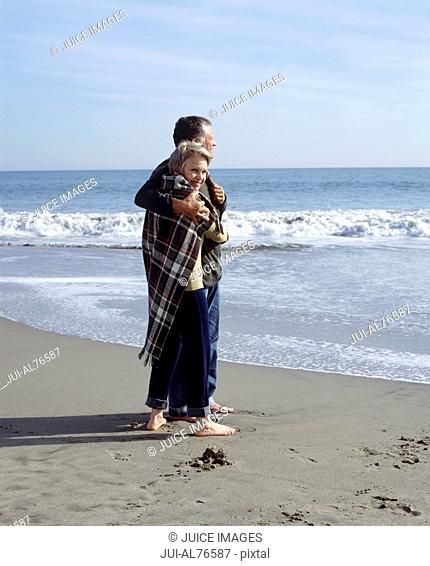 View of a couple embracing on the beach