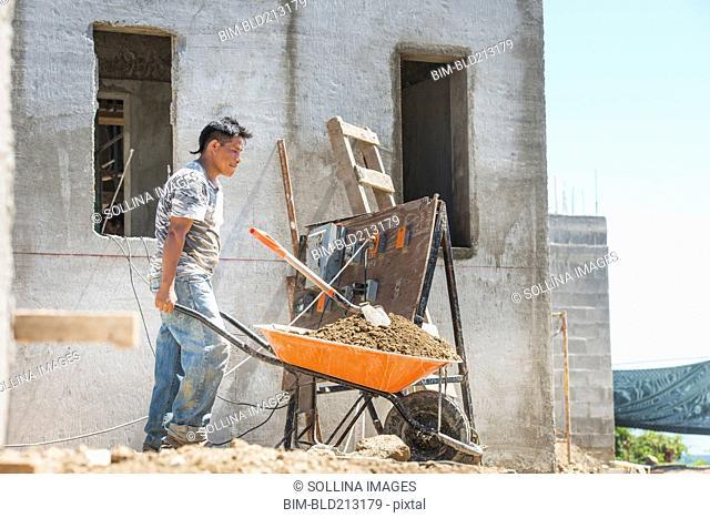 Hispanic construction worker pushing wheelbarrow at construction site