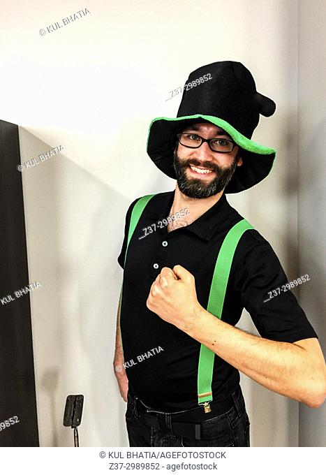 A youngman dressed in black and green, the colours of St. Patrick's day, mugs for the camera, Ontario, Canada