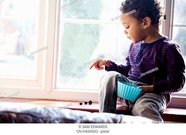 Cute, innocent boy counting snacks in windowsill