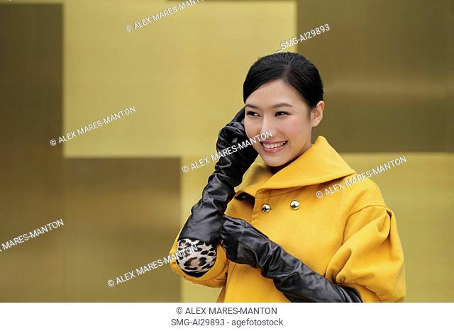 Young woman in coat and gloves talking on phone