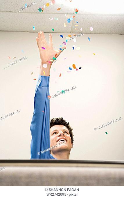 Businessman throwing confetti