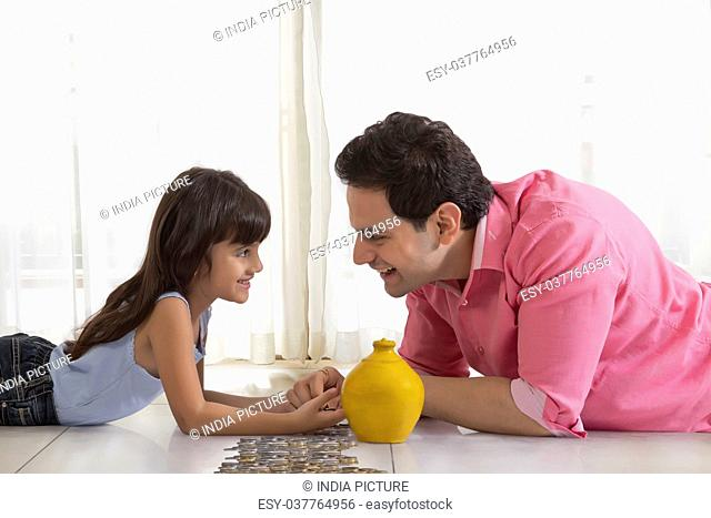 Father and daughter lying on floor with piggy bank counting change