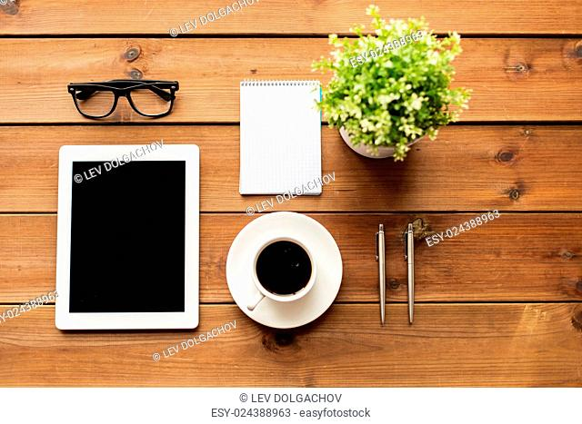 education, business and technology concept -close up of tablet pc computer, coffee cup, eyeglasses and notepad on wooden table
