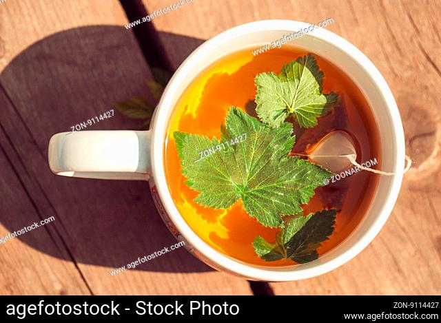 Top view of tea with currant leaf in white cup