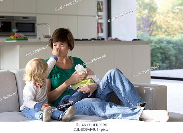 Mother, baby boy and female toddler sitting on sofa
