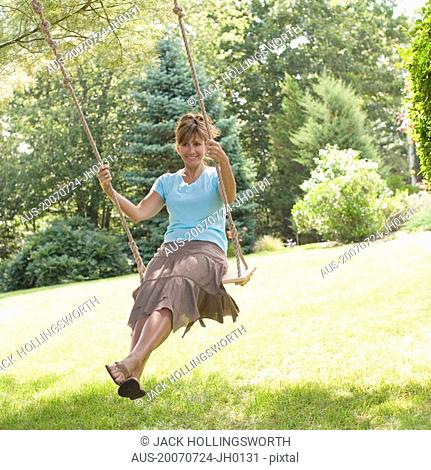 Mature woman swinging on a rope swing