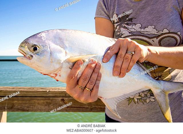 USA, Texas, Mature woman holding fresh caught Florida Pompano fish