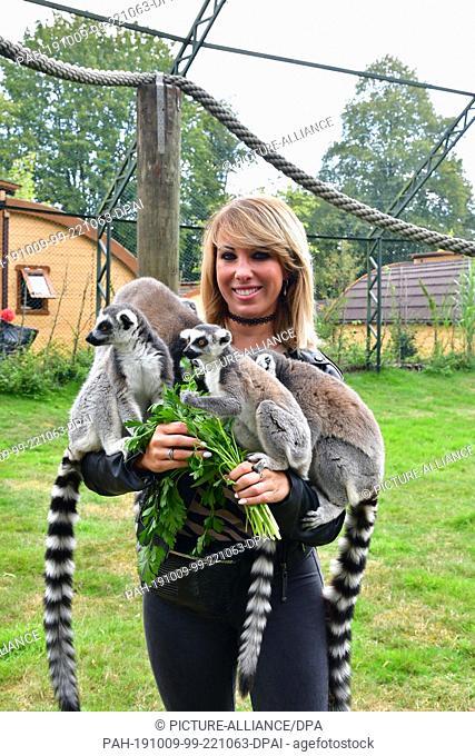 07 September 2019, Lower Saxony, Hodenhagen: Annemarie Eilfeld in the Serengeti-Park Hodenhagen caresses and feeds calicoes