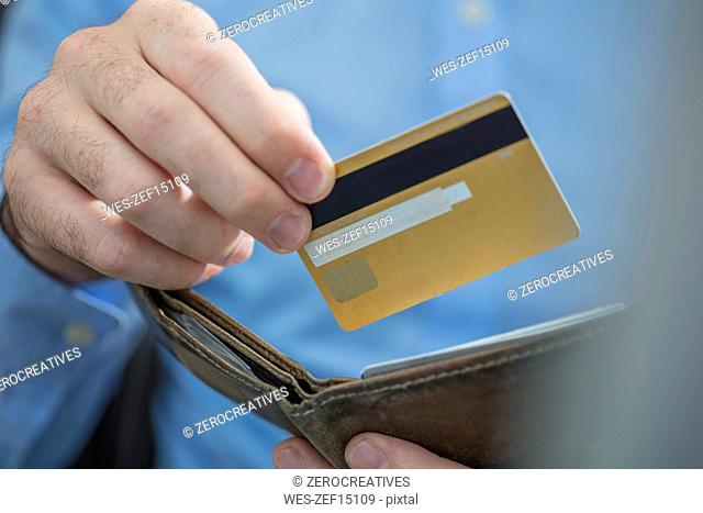 Man's hands holding credit card and purse, close-up