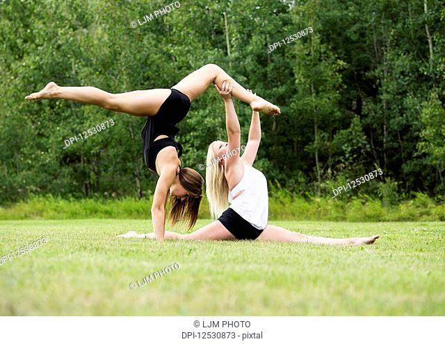 Two Teenage Gymnists Practicing Their Routines Outdoors In A Park And Doing A Handstand Straddle Balance While The Other Partner Does A Split; Edmonton, Alberta