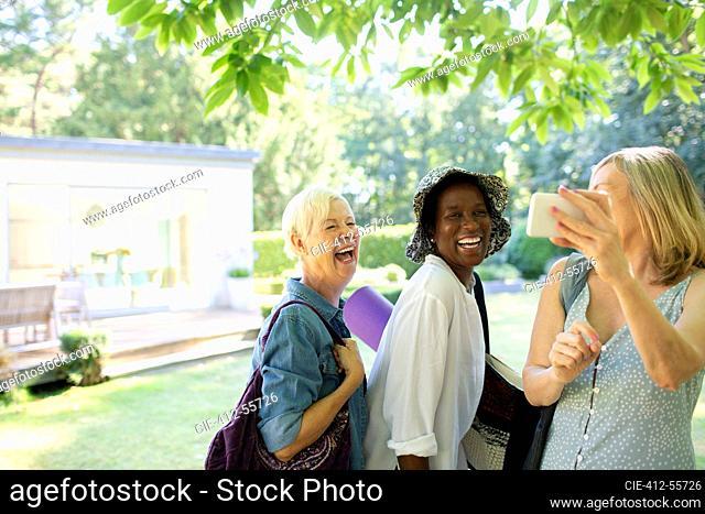 Happy senior women friends taking selfie in summer garden