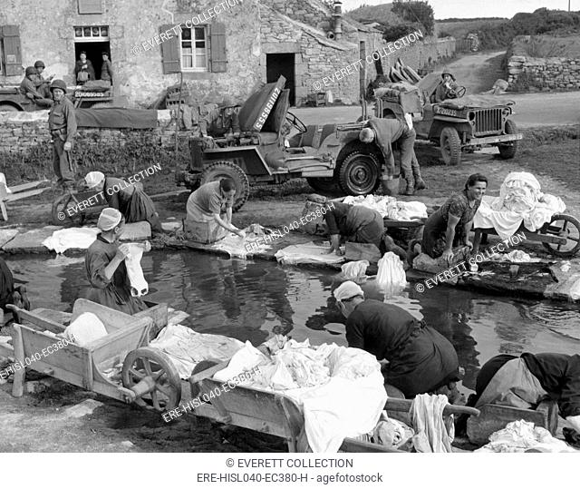 French village women doing their share their laundry facility with GI's washing their Jeep. Sept. 20, 1944, World War 2 (BSLOC-2015-13-84)