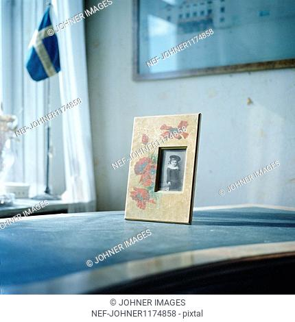 Picture frame on table, Swedish flag in background