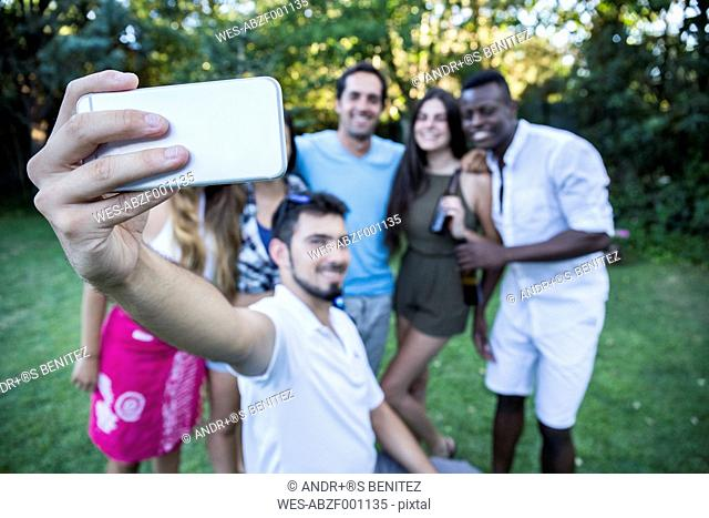Friends taking a selfie in a garden during a summer party