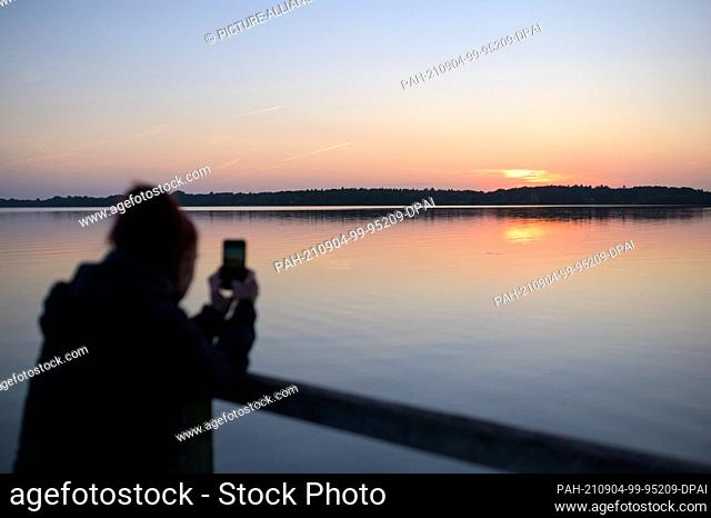 04 September 2021, Lower Saxony, Bad Zwischenahn: A woman photographs the sunset at the Zwischenahner Meer with her mobile phone