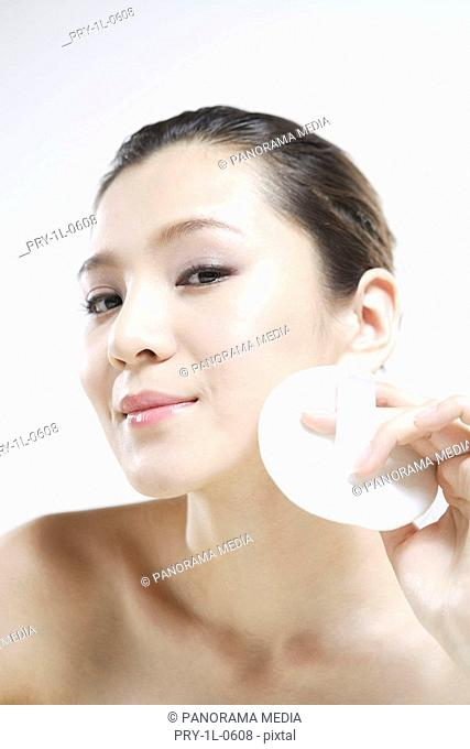Young woman making up