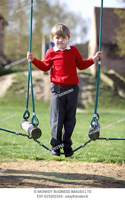 Male Elementary School Pupil On Climbing Equipment