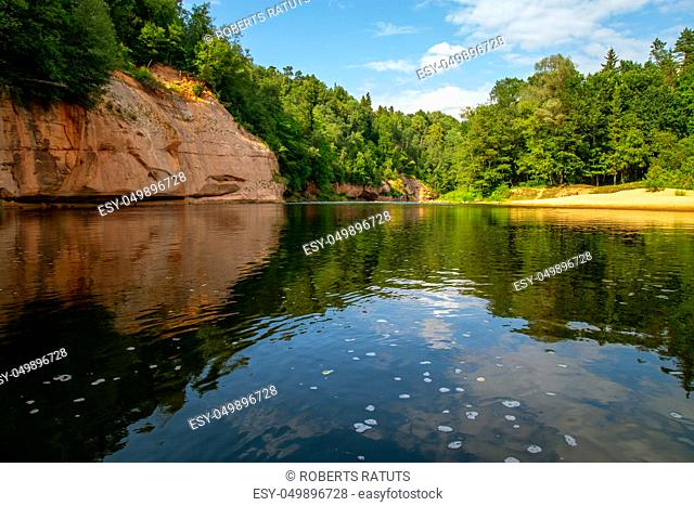 Landscape with cliff near the river Gauja, forest and clouds reflection in water. The Gauja is the longest river in Latvia