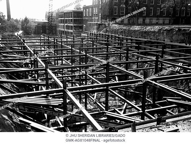 During the early stages of construction of the Milton S Eisenhower Library at Johns Hopkins University, steel beams are stacked and arranged into place from the...