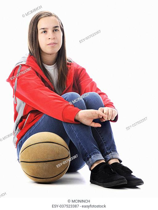 A senior high school athlete sitting on the floor waiting to play basketball, with the ball at her side. On a white background