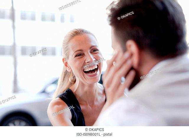 Mature man and woman, face to face, woman touching man's face, laughing