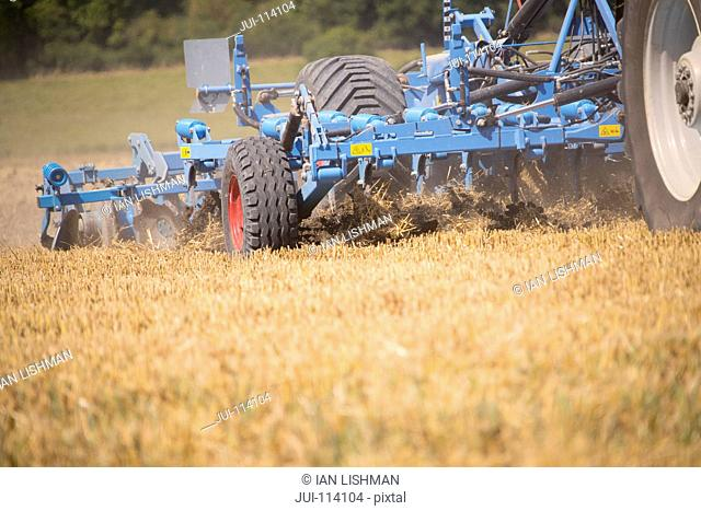 Close Up Of Tractor Ploughing Field Using Disc Plough