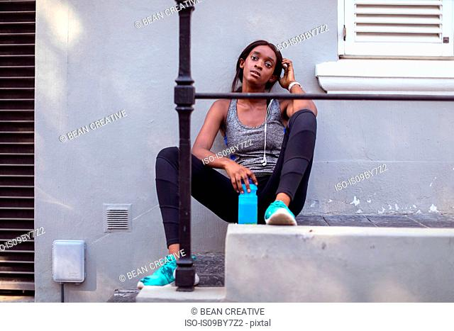 Young female runner sitting on city sidewalk stairs, portrait