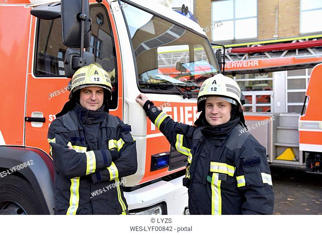Portrait of two confident firefighters in front of fire engine