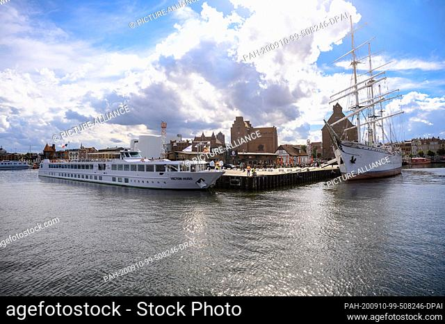 "29 August 2020, Mecklenburg-Western Pomerania, Stralsund: The inland cruise ship """"Victor Hugo"""" and the museum ship """"Gorch Fock 1"""" are moored in the harbour"
