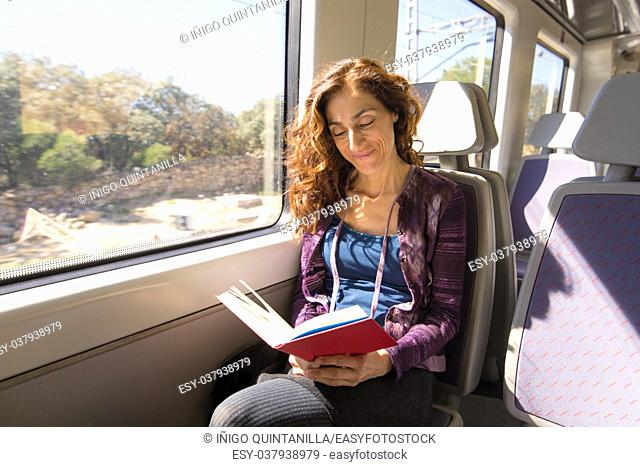 red hair smiling woman dressed in purple and blue, traveling by train sitting reading red open book, with happy face