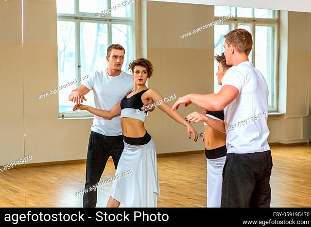 beautiful couple dancing tango. young woman in black and white dress and man in sport clothes practicing in dancing studio mirror room. copy space
