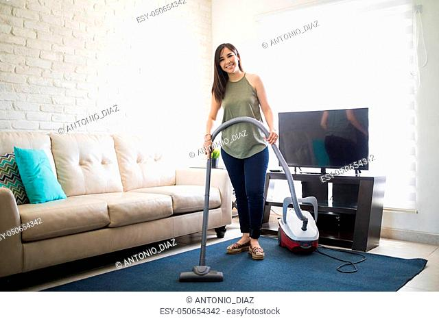 Full length of a beautiful young housewife cleaning house mat in living room using vacuum cleaner