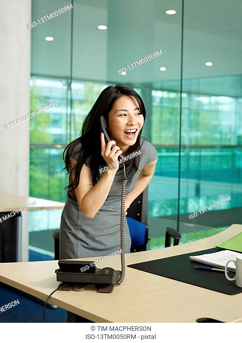 A girl laughs while on the phone