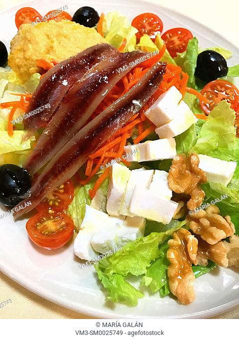 Mixed salad made of lettuce, cherry tomatoes, anchovies, black olives, cottage cheese, red pepper, nuts and olive oil. Spain