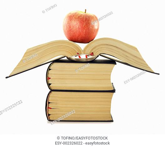 Composition with stack of books and apple isolated on white