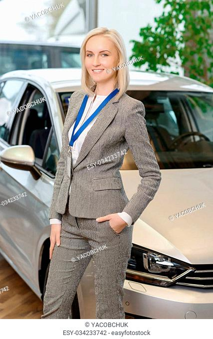 Ready to sell. Nice-looking young sales representative is smiling pleasantly while posing in front of a car