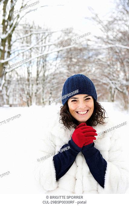 Woman in snowy woods rubbing her hands