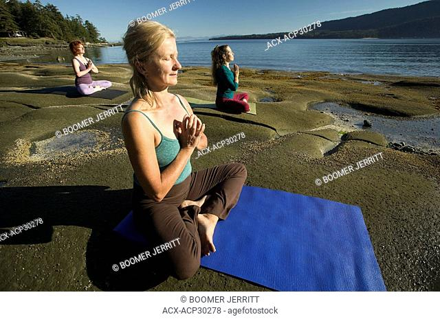 Yoga practioners meditate and relax in the lotus position. Denman Island, The Comox Valley, Vancouver Island, British Columbia, Canada