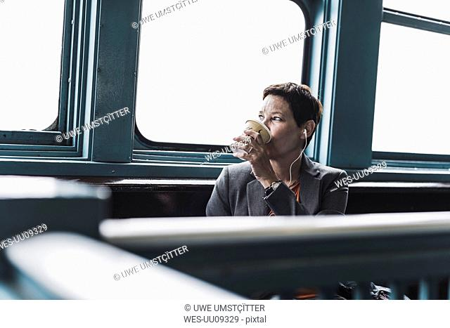 Businesswoman on a ferry drinking coffee