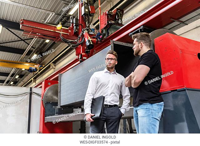 Two men standing and talking on factory shop floor