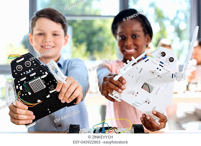 Bright smiles. Happy pre-teen boy and girl standing in the robotics classroom and posing with their robot models, having created them by themselves