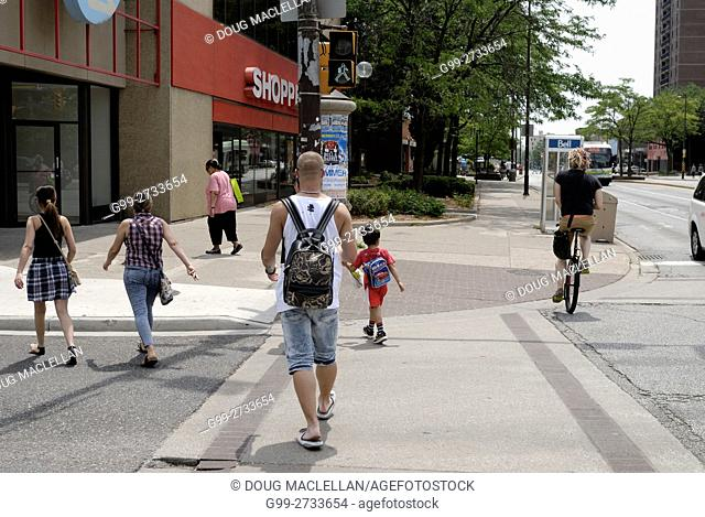 Three women, a child, a man and a male unicycle rider cross at a downtown intersection in Windsor, Ontario